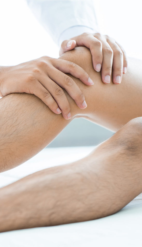 Osthepathe qui manipule la jambe d'un patient au CEESO Paris