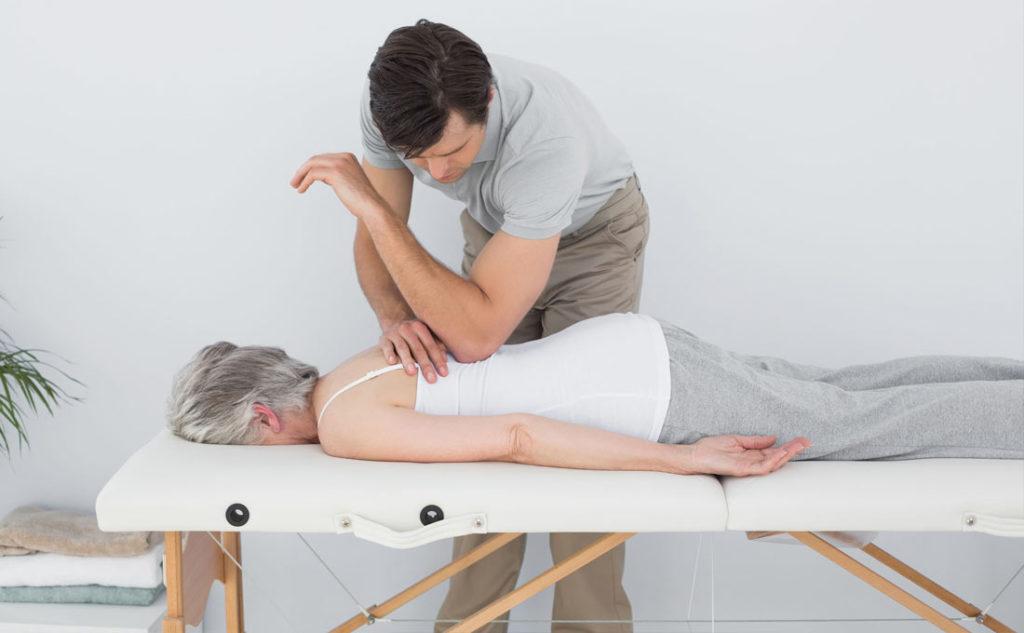 Ostéopathe en train de manipuler une personne agée